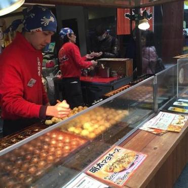 Takoyaki, fried dough usually stuffed with minced octopus, being cooked and sold in Kuromon Market in Osaka.
